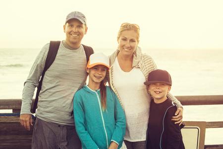 Glimlachende gelukkige familie die van hun tijd genieten samen tijdens een de zomerreis naar de oceaan. Samen staan met de zonsondergang achter hen terwijl ze genieten van hun tijd samen