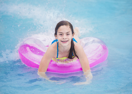 Cute girl smiling and having fun playing in the swimming pool during summer. Happy9 year old girl with braces and an adorable smile sitting on an inflatable floating tube