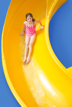 Smiling Young girl riding down a yellow water slide