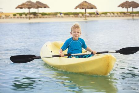 Jonge actieve Jongen die een oceaankayak paddelt bij het strand terwijl op een tropische vakantie. Kind plezier een schilderachtige strandresort met ligstoelen en cabanas op de achtergrond