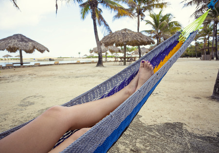 Mooie vrouwelijke voeten en benen ontspannen in een blauwe hangmat op het strand.