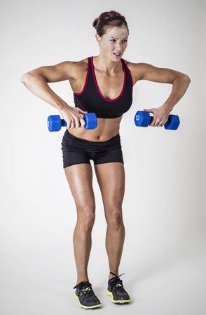 Mooie sterke gespierde vrouw opheffing halter vrije gewichten in een indoor gym. Ernstige vrouwelijke lichaamsbouwer doet biceps krullen training volledige lengte