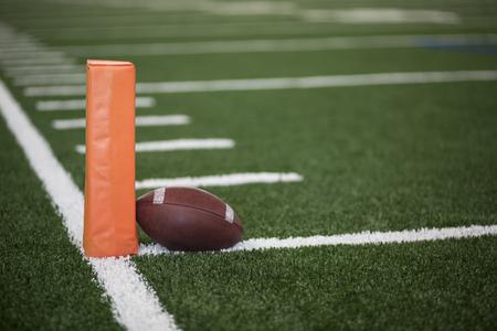 Bal die op de doellijn van een endzone van het Voetbalgebied naast een oranje pyloon rust Stockfoto - 92863125