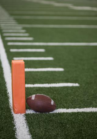 Selectieve focusfoto van de pyloon en touchdownlijn op een voetbalveld. Lage hoekmening van de eindstreek in een binnenstadion