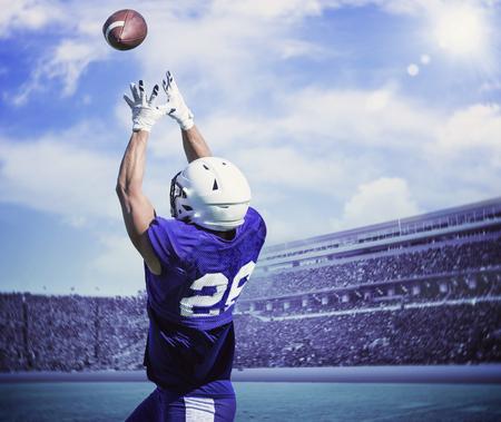 American Football Player Catching a touchdown Pass in a large outdoor football stadium Stock Photo