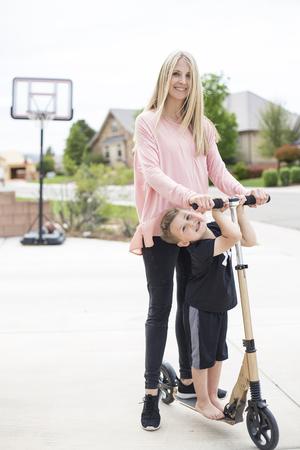 Leuke jonge moeder en haar kleine jongen die samen op een autoped op de oprijlaan in een buurt in de voorsteden spelen.