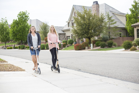 Twee glimlachende aantrekkelijke vrouwen die pret berijdende autopedden samen langs een stoep in een mooie buurt hebben Stockfoto