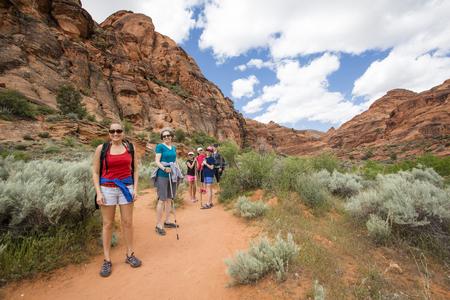 Glimlachende groep wandelaars die van de dag genieten die samen langs een mooie wandelingssleep van de woestijnklip wandelen in Utah.