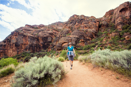 Happy senior woman hiking in a red rock sandstone canyon. The active, retired woman is enjoying a walk along a scenic trail with vibrant red rock cliffs in the background.