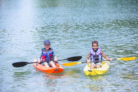 Twee verschillende jongens die samen op het meer kajakken Stockfoto - 92863966