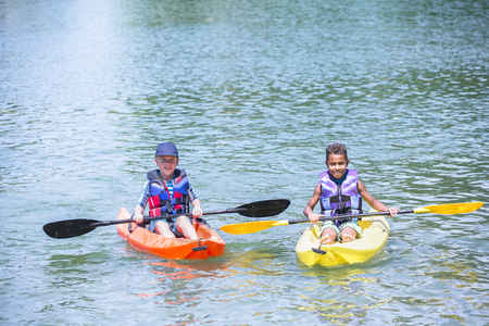 Two diverse boys kayaking together on the lake Banco de Imagens