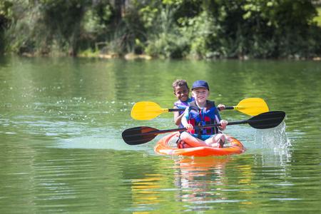 Two diverse little boys kayaking down a beautiful river Banco de Imagens
