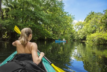 Adventuresome Woman kayaking along a beautiful tropical jungle river. Paddling along a calm beautiful river in a scenic natural backdrop Archivio Fotografico