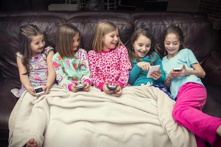 Groep leuke, gelukkige kleine meisjes die met hun slimme telefoons samen spelen terwijl het zitten op de laag bij een logeerpartij. Vijf meisjes die allemaal verbinding maken met sociale media en samen reageren op grappige inhoud Stockfoto