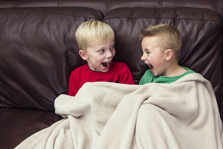 Two excited and happy boys laughing together as they sit on the couch watching television. Stock Photo - 92864905