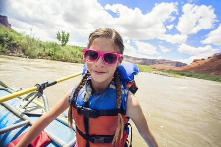 Jong meisje dat pret op een rivier het raften reis onderaan de Rivier van Colorado heeft