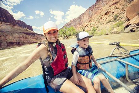 Actieve jonge familie die van een dag genieten die neer rafting een whitewaterrivier samen. De moeder en de zoon die samen op een groot vlot zitten die een rode rotscanion drijven Stockfoto