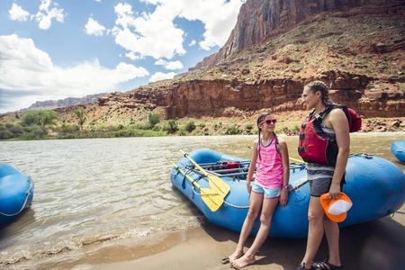 Lachende kind en volwassen vrouwen klaar om aan boord te gaan van een groot opblaasbaar vlot terwijl ze door de schilderachtige Colorado-rivier reizen nabij Moab, Utah en Arches National Park Stockfoto