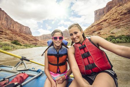 Actieve jonge familie die van een dag genieten die neer rafting een whitewaterrivier samen. De moeder en de dochter zitten samen op een groot vlot dat in een rode rotskloof drijft