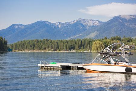 Mooie zomerscène van een motorboot die bij een bootdok op een mooi, schilderachtig bergmeer wordt geparkeerd. Blauwe lucht, blauwe bergen, blauw water