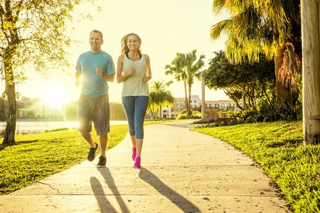 Man en vrouw oefenen en joggen samen in het park. Gelukkig en glimlachend als ze langs het pad lopen tijdens zonsondergang op een warme zomerdag Stockfoto