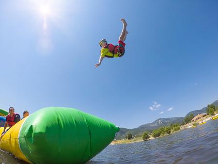 Jonge jongen die in de lucht door in opblaasbaar waterstuk bij het meer op een warme de zomerdag wordt gelanceerd. Hij heeft een leuke uitdrukking omdat hij verrast is hoe hoog hij door de lucht vliegt