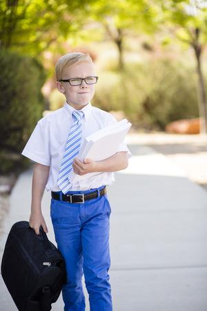 Abstracte foto van een jonge jongen die ook een leuke, maar ernstige en slimme zakenman is die aan het werk loopt die documenten en een aktentas draagt. Hij is ook een geweldige student