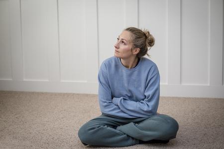 vrouw diep in gedachten worstelt met depressie terwijl ze probeert te mediteren of te bidden in haar huis. Abstracte foto van een vrouw die het leven` s uitdagingen overweegt Stockfoto