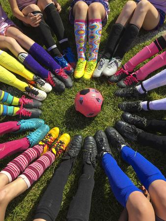 Club soccer team sitting around a soccer ball Banco de Imagens