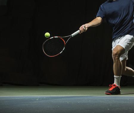 Sluit omhoog foto van een mens die een tennisracket slingert tijdens een tennisgelijke