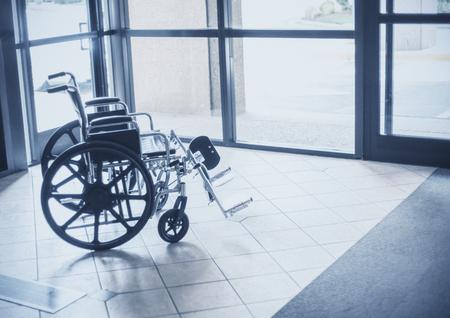 Solitaire rolstoel die in de hal van een ziekenhuis rust. Abstract beeld van gezondheidszorg en invaliditeit Stockfoto