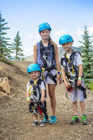 Glimlachende groep leuke kinderen klaar om op een zip-line avontuur in de bergen te gaan terwijl ze samen op een zomervakantie zijn Stockfoto