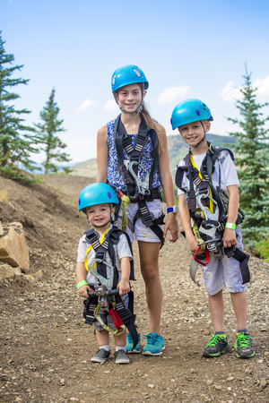 Smiling group of cute kids ready to go on a zip line adventure in the mountains while on a summer vacation together