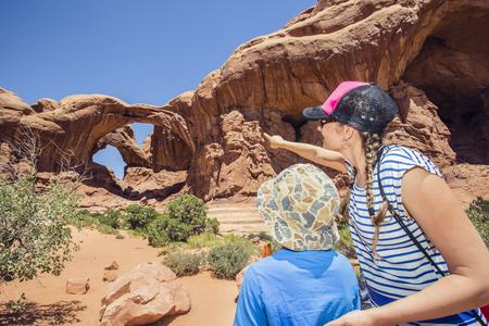 Achteraanzicht van een familie die tussen de rode rotsformaties in de buurt van Moab, Utah en het Arches National park wandelt. Samen de natuurlijke wonderen van de Verenigde Staten verkennen.