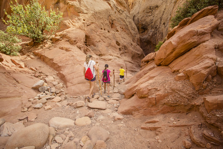 Family hiking together in a sandstone slot canyon near Arches National Park Banco de Imagens