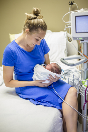 Glimlachende Moeder die haar pasgeboren voorbarige baby in het ziekenhuis houdt