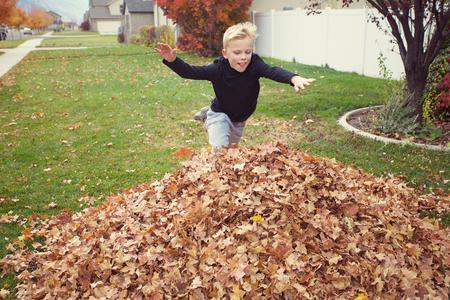 Leuke jonge jongen die in een grote stapel van bladeren op een dalingsmiddag springt. Plezier buiten spelen Stockfoto
