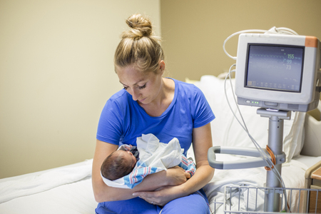 Young mother holding her Premature newborn baby who is being treated in the hospital. With love and tenderness she holds her baby close while sitting on a hospital bed next to a vital signs monitor 写真素材