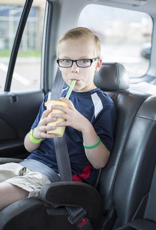 Leuke jongenszitting in een hulpzetel op een lange autorit die een smoothie drinkt terwijl veilig vastgebonden in een autozetel. Hij draagt ??zijn veiligheidsgordel en geniet van een drankje. Stockfoto
