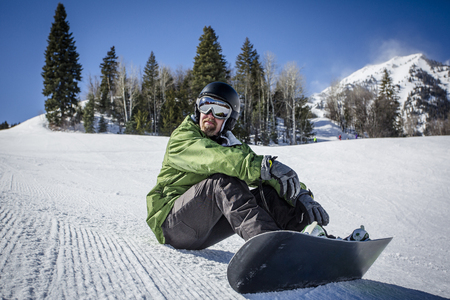 Male adult snowboarder enjoying a day at a ski resort while rest on a perfectly groomed ski slope. A beautiful day on the slopes having fun