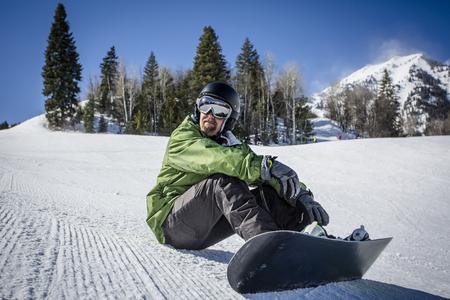 Mannelijke volwassen snowboarder die van een dag geniet bij een skitoevlucht terwijl rust op een perfect verzorgde skihelling. Een mooie dag op de hellingen met plezier