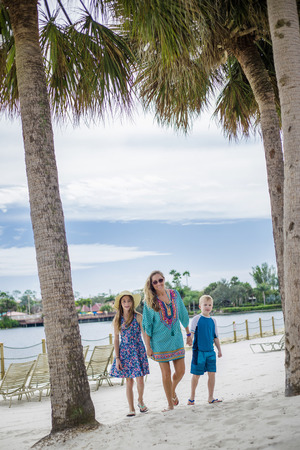 Familie die samen op een strand bij een tropische strandtoevlucht loopt