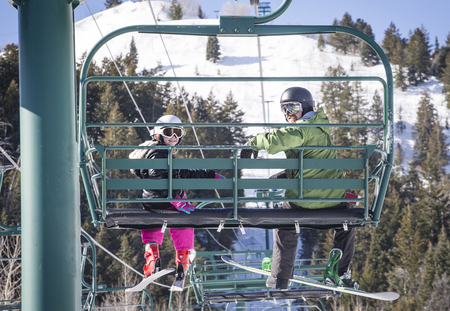 Smiling father and daughter riding a chair lift together on a sunny day at a ski resort Banco de Imagens