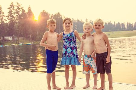 Vier schattige kinderen genieten van hun zomervakantie samen aan het meer. Samen spelen op het dok bij zonsondergang op een warme avond
