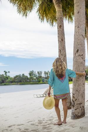 Mooie vrouw die in sundress op een tropisch strand loopt. Mening van erachter van een schitterend wijfje die van een mooie dag genieten bij een tropische strandtoevlucht