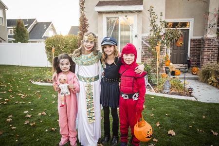 Groep van kinderen gekleed in Halloween-kostuums gaan trick or treat buiten in oktober in een ingerichte wijk