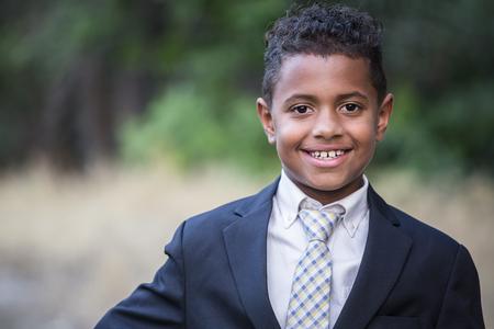 Portret van een knappe jonge Afro-Amerikaanse jongen in formele kleding. Glimlachend met zijn armen over elkaar en draagt een pak en stropdas
