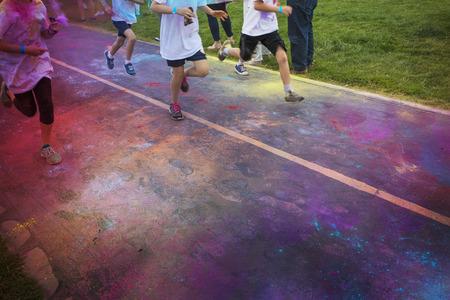 Abstracte foto van een groep agenten die in een kleur lopen race-evenement. Geen gezichten zichtbaar op de benen en de voeten en schoenen van de hardloper. Veel kleurrijke krijtwolken in de lucht en op straat