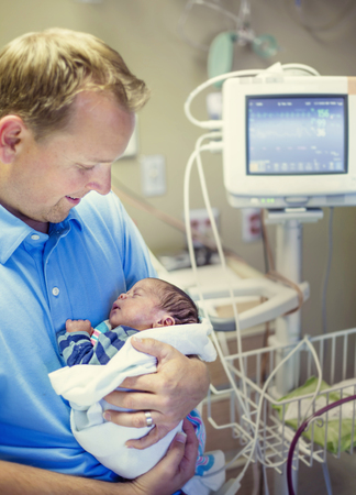 Jonge glimlachende vader die haar Voorbarige pasgeboren baby houdt die in het ziekenhuis wordt behandeld. Met liefde en tederheid houdt hij zijn baby dicht in een ziekenhuiskamer naast een monitor voor vitale functies Stockfoto - 92987292
