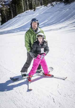 Glimlachende vader en dochter die en samen bij een skitoevlucht op een mooie dag ski? En ski? En. Plezier hebben terwijl hij haar lesgeeft in skiën